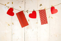 Red hearts and envelopes hanging on cord on wooden background
