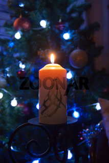 A large candle burns against the background of a garland with shining lights. Vertical photo, defocus. Mystic esoteric romance divination mood christening Christmas carol setcers.
