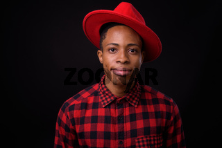 Young handsome African hipster man against black background