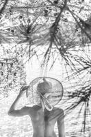 Rear view of topless beautiful woman wearing nothing but straw sun hat realaxing on wild coast of Adriatic sea on beach in shade of pine tree. Relaxed healthy lifestyle concept. Black and white image
