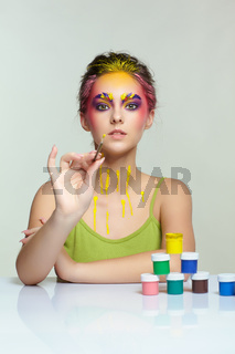 Portrait of young woman posing at the table with pyramid of small cans of paint and brush in hand.