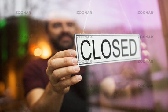 owner puts closed sign at bar or restaurant window