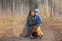Happy mother and son in autumn forest