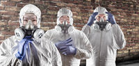Chinese and Caucasian Woman and Men In Gas Masks, Goggles and Hazmat Suites Against Brick Background