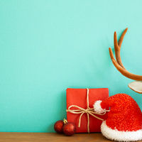 Christmas concept. Red gift box with bauble, santa claus hat, deer's antler on wooden table with green background