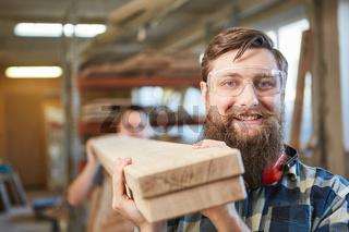 Hipster mit Bart als Tischler Lehrling trägt Balken