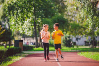 Child fitness, twins kids running on stadium track in city park , training and children sport healthy lifestyle. Outdoor activities by running make the child's body healthy and experience enriched