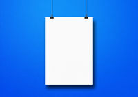 White poster hanging on a blue wall with clips
