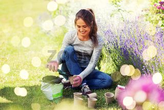 woman filling pots with soil at summer garden