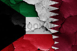 flags of Kuwait and Qatar painted on cracked wall