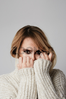 Vertical portrait of young woman wearing warm sweater. Winter concept.