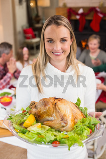 Portrait of a smiling woman showing the roast turkey