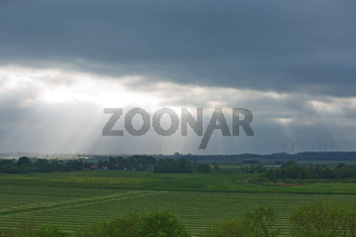 Beautiful countryside and sunrays passing through clouds on landscape with fields near Kiel - Schleswig-Holstein - Germany