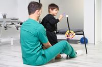 Child with cerebral palsy on physiotherapy in a children therapy center. Boy with disability doing exercises with physiotherapists in rehabitation centre.