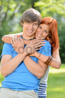 Young loving couple hugging in sunny park