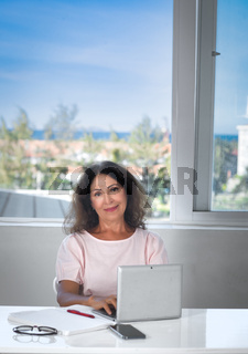 Portrait of a beautiful senior woman working at home