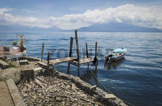 Wooden seat at jetty along lake Atitlan at the coast of Santa Cruz la Laguna, Guatemala