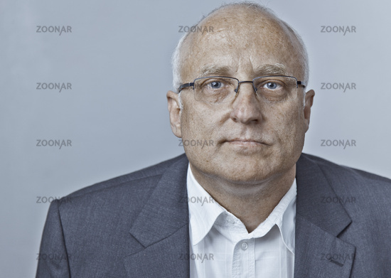 Portrait of a middle-aged man with glasses looks expectant and convinced