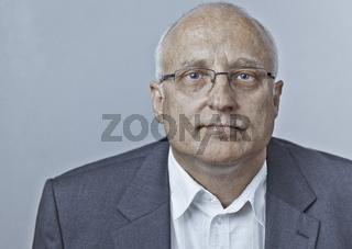 Porträt eines Mannes mittleren Alters mit Brille blickt erwartungsvoll und überzeugt