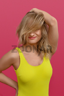 Blond woman laughing in yellow swimsuit