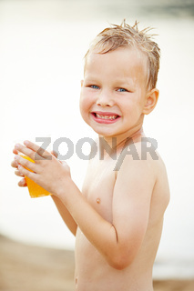 Kind am Strand trinkt Saft