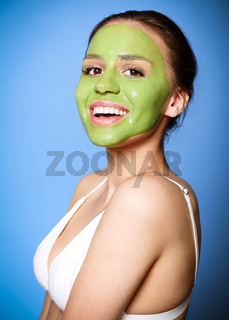 Cheerful woman with green mask