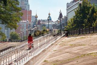 A woman with a stroller climbs a long metal ramp