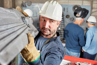 Arbeiter beim Tragen von Lasten in Werkstatt
