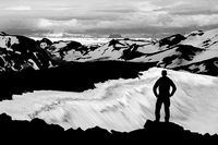 Hiker Man Silhouette enjoying view from Ok Vulcano crater to the snow Mountains of Thorisdalur. Monochrome, Black and White, Iceland.