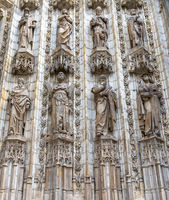 architectural detail of the door decorations and statues of the historic cathedral in Seville