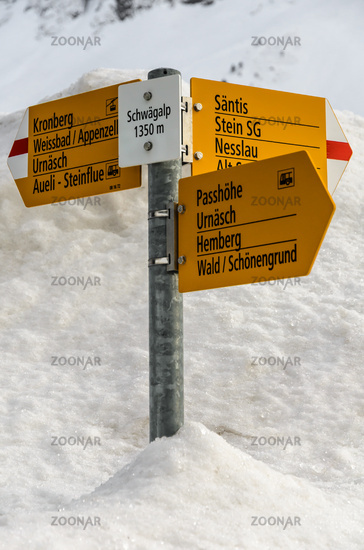 Trail sign with various hiking destinations on the Schwaegalp in snow, Switzerland
