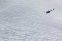 Shadow from helicopter on snowy off piste ski slope with traces from skis and snowboard