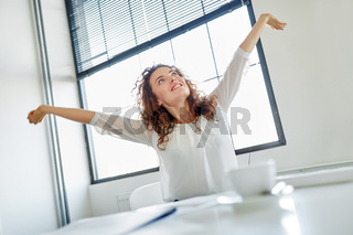 Frau macht Dehnübung für Rücken im Büro
