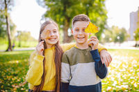 Friendship between siblings. Siblings together outside with bright colored background. Kids autumn portrait. Brother and sister playing in autumn park leaves. Family active fall weekend concept