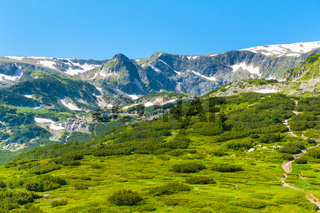 Spring green foliage and snow Mountains by Rila Lakes in Bulgaria