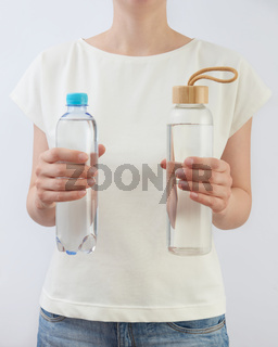 Two bottles of glass and plastic of clean fresh water in a woman's hands.