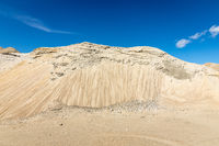 Sand in a big sand pit, with blue sky and white clouds in the background, hill looks like a mountain