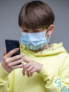 Junge mit Mundschutzmaske und Smartphone