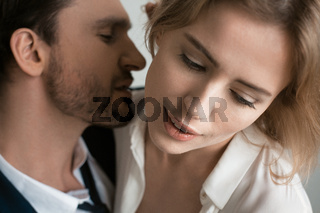 Man with bristles in a suit with a young mistress in a white blouse. Passionate relationship between colleagues. High quality photo