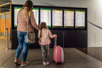 Defocused silhouette of family, young girl and her mother on airport terminal