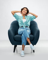 happy smiling young woman sitting in armchair
