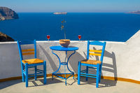 Two Glasses and Two Chairs on a Sunny Rocky Shore