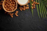 Amond seeds in wooden bowl, fresh natural milk placed on black stone background