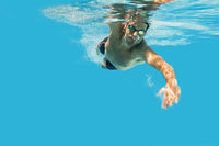 Pro swimmer in the swimming pool. Underwater swim photo with copy space.