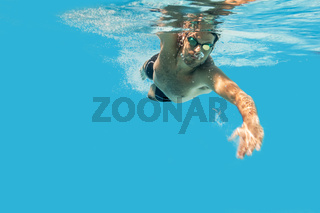 Pro male swimmer in the swimming pool. Underwater swim photo with copy space.