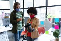 Two diverse business colleagues wearing face masks using camera in creative office
