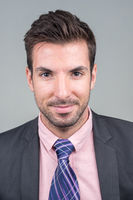 Portrait of young handsome Hispanic businessman in suit