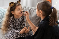 girls doing face painting on halloween at home