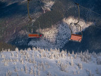 Alpine resortr ski lift with seats going over the sunset mountain skiing freeride slopes and fir tree groves