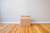 cardboard box in empty room,on wooden floor in new flat